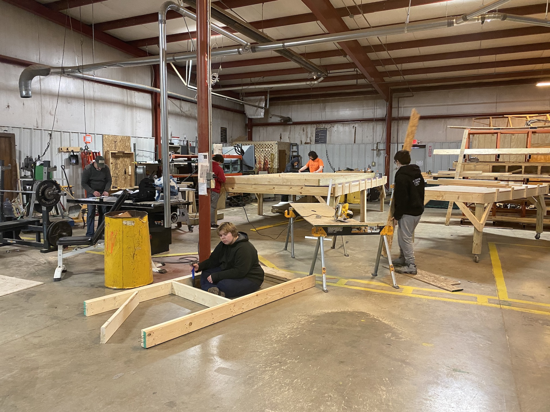 Students working in woodworking shop building tiny shelters
